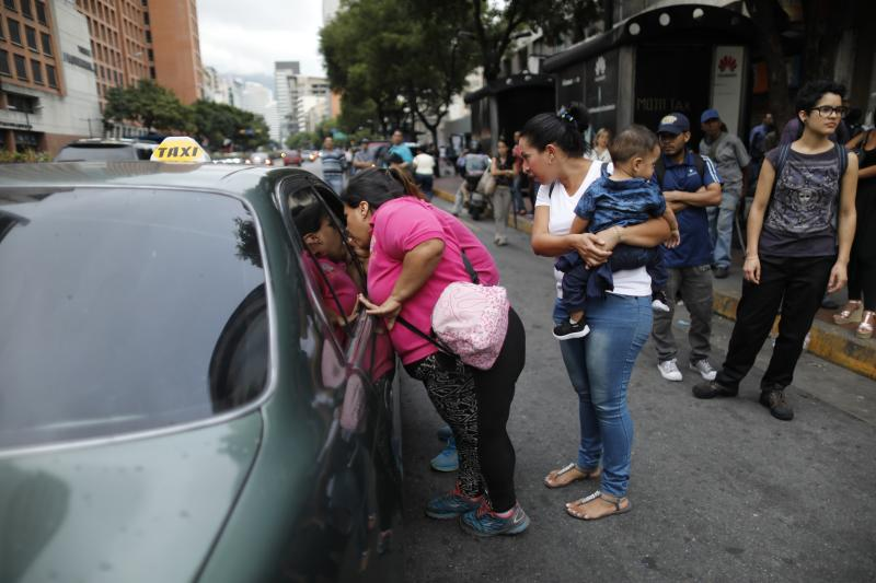 People ask a taxi driver how much it is to take them to their neighborhood during a blackout in Caracas, Venezuela, Monday, July 22, 2019. The lights went out across much of Venezuela Monday, reviving fears of the blackouts that plunged the country into chaos a few months ago as the government once again accused opponents of sabotaging the nation's hydroelectric power system. (AP Photo/Ariana Cubillos)