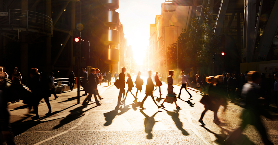 City workers cross a street at sunset.