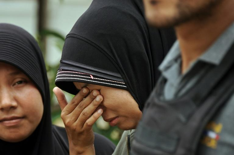The wife of a Muslim man who was shot dead reacts as Thai police officers inspect his body in the Rangae district of Thailand's restive southern province of Narathiwat on October 5, 2015
