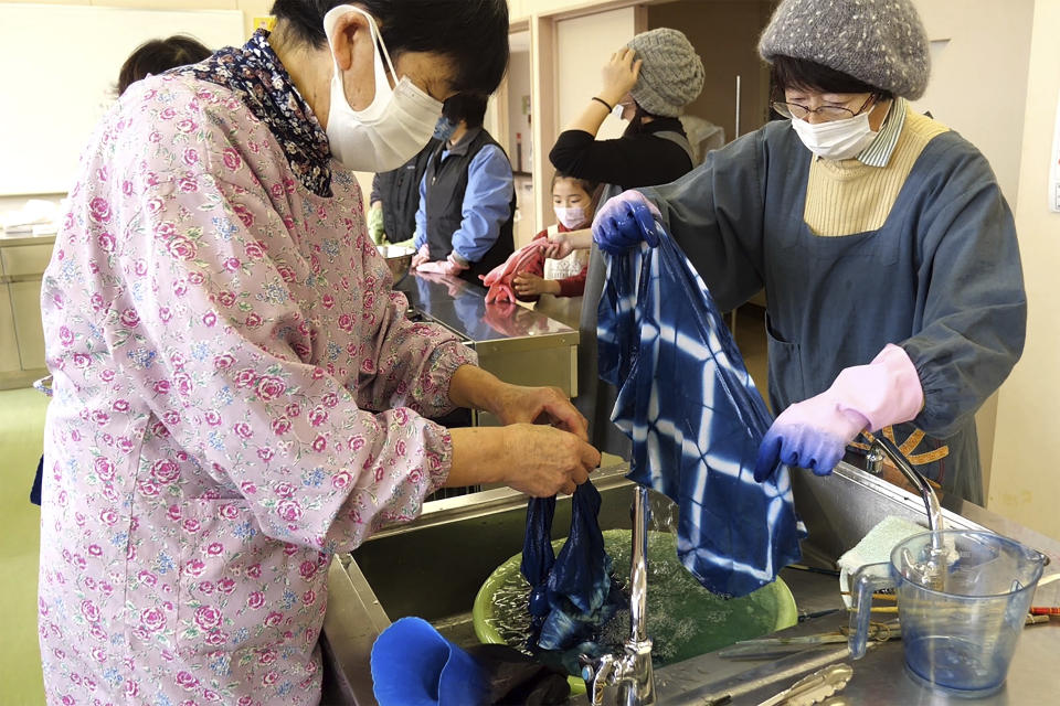 In this image from video, members of Japan Blue wash off dyed handkerchiefs at a community center which was used as an evacuation center when the massive earthquake hit the area in 2011, in Minamisoma, Fukushima Prefecture, northeastern Japan, on Feb. 21, 2021. Because of radiation released by the Fukushima nuclear plant disaster a decade ago, farmers in nearby Minamisoma weren't allowed to grow crops for two years. After the restriction was lifted, two farmers found an unusual way to rebuild their lives and help their destroyed community. They planted indigo and soon began dying fabric with dye produced from the plants. A group called Japan Blue holds workshops that have taught indigo dyeing to more than 100 people each year. (AP Photo/Chisato Tanaka)