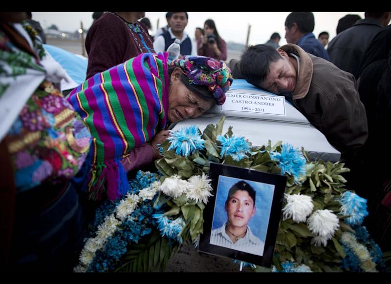 Natalia Andres Lopez, left, and another relative, mourn over the coffin containing the body of her cousin, at an Air Force base in Guatemala City , Wednesday, March 21, 2012. (AP Photo/Rodrigo Abd)