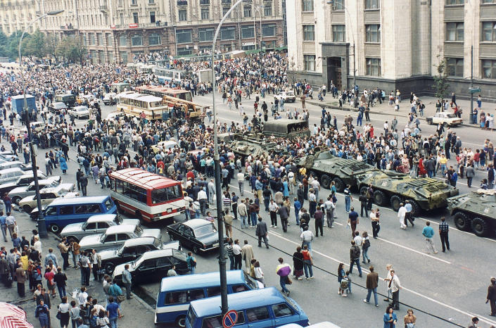 FILE - In this Monday, Aug. 19, 1991 file photo, Soviet tanks are surrounded by anti-coup demonstrators in an attempt to prevent them from moving into Moscow's Red Square, Russia. When a group of top Communist officials ousted Soviet leader Mikhail Gorbachev 30 years ago and flooded Moscow with tanks, the world held its breath, fearing a rollback on liberal reforms and a return to the Cold War confrontation. But the August 1991 coup collapsed in just three days, precipitating the breakup of the Soviet Union that plotters said they were trying to prevent. (AP Photo/Boris Yurchenko, File)