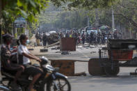 Riot policemen approach a section of the road blocked by anti-coup protesters with debris in Mandalay, Myanmar, Tuesday, March 2, 2021. Demonstrators in Myanmar took to the streets again on Tuesday to protest last month's seizure of power by the military, as foreign ministers from Southeast Asian countries met to discuss the political crisis. Police in Yangon, Myanmar's biggest city, used tear gas and rubber bullets against the protesters. (AP Photo)