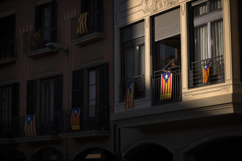 """In this photo taken on Saturday, Nov. 10, 2012, a woman fixes a pro-independence """"estelada"""" flag on her balcony in Vic, a town declared by the city council a """"free Catalan territory"""" in Spain. Catalonia holds elections on Sunday that will be seen as a test of the regional government's plans to hold a referendum on independence, and one of the key issues emerging is the theoretical place of a free Catalonia in Europe. (AP Photo/Emilio Morenatti)"""