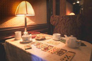 Playing cards are laid out on a table with tea service cups in a vintage Pullman carriage. Photo: Orient Express
