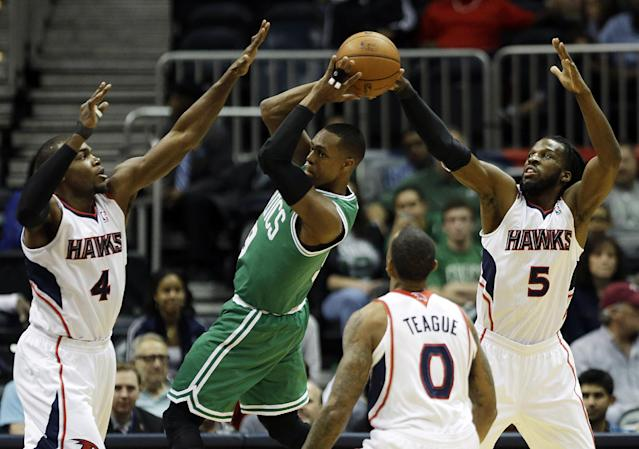 Boston Celtics' Rajon Rondo, center, looks to pass the ball against the defense of Atlanta Hawks' Paul Millsap, from left, Jeff Teague and DeMarre Carroll, in the first quarter of an NBA basketball game, Wednesday, April 9, 2014, in Atlanta. (AP Photo/David Goldman)
