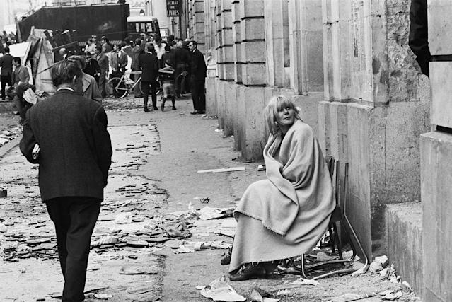 <p>A woman sits in a chair on Rue des Saints Pères, near l'École de Médecine on May 11, 1968, a day after student clashes with police in the Latin Quarter of Paris. (Photo: Gökşin Sipahioğlu/SIPA) </p>