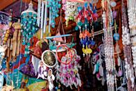 """<p><strong>Why this market in particular?</strong><br> Sukawati Art Market is a cheaper and quieter alternative to nearby <a href=""""https://www.cntraveler.com/shops/bali/ubud-art-market?mbid=synd_yahoo_rss"""" rel=""""nofollow noopener"""" target=""""_blank"""" data-ylk=""""slk:Ubud Market"""" class=""""link rapid-noclick-resp"""">Ubud Market</a> and other popular locales in southern Bali. There is an impressive array of handcrafted artworks for sale, from framed paintings of local farm life to large wooden sculptures of Hindu deities. Without the intimidating crowds, it's an ideal place to flex your bargaining skills.</p> <p><strong>What can we expect to find in the stalls?</strong><br> There's a sufficient variety and volume of goods to peruse: carved figurines, necklaces, artisanal bowls, canvas art, game boards, clothing, woven textiles, and so much more.</p> <p><strong>If we're in the mood for a splurge, what should we look for?</strong><br> Lovely person-sized wooden sculptures, though remember, you'll also need to foot the cost for shipping them home.</p> <p><strong>And … for a more budget souvenir?</strong><br> Vibrant patterned dresses and accessories for fashionistas; home goods like wooden chimes and natural wood kitchenware for the domestic-minded, and tote bags for all tastes.</p> <p><strong>Who else shops here?</strong><br> You'll find other value-driven tourists scoping for smart souvenirs and clothing. You'll also rub shoulders with local Balinese who shop here regularly.</p>"""