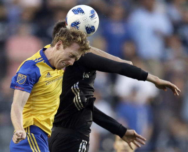 Colorado Rapids midfielder Jack McBean, front, heads the ball next to Sporting Kansas City midfielder Ilie Sanchez, back, during the first half of an MLS soccer match in Kansas City, Kan., Saturday, May 5, 2018. McBean received a yellow card on the play. (AP Photo/Orlin Wagner)