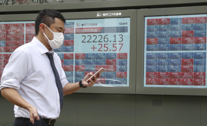 A man walks by an electronic stock board of a securities firm in Tokyo, Monday, April 22, 2019. Asian stock markets were mixed Monday following the Easter holiday weekend as investors looked ahead to U.S. and Japanese economic data. (AP Photo/Koji Sasahara)