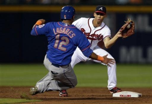 Atlanta Braves shortstop Andrelton Simmons, right, prepares to tag out New York Mets' Juan Lagares (12) on a steal-attempt in the fifth inning of a baseball game on Thursday, June 20, 2013, in Atlanta. (AP Photo/John Bazemore)