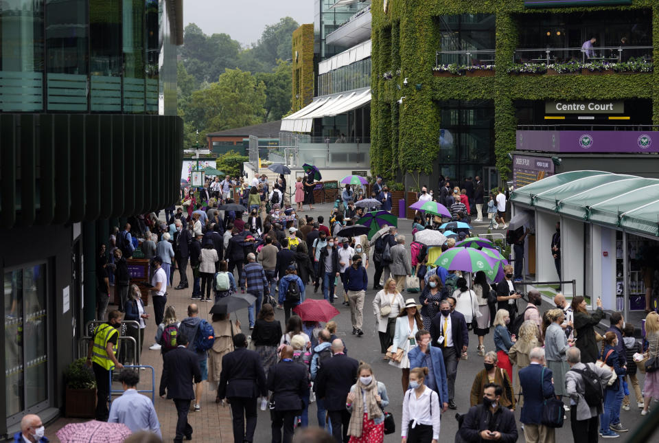 Crowds walk around the grounds during a rain delay on day one of the Wimbledon Tennis Championships in London, Monday June 28, 2021. (AP Photo/Kirsty Wigglesworth)
