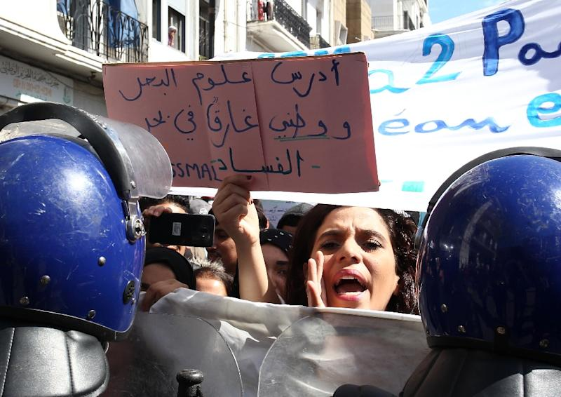 """An Algerian protester holds sign that reads """"My country is drowning in a sea of corruption"""""""