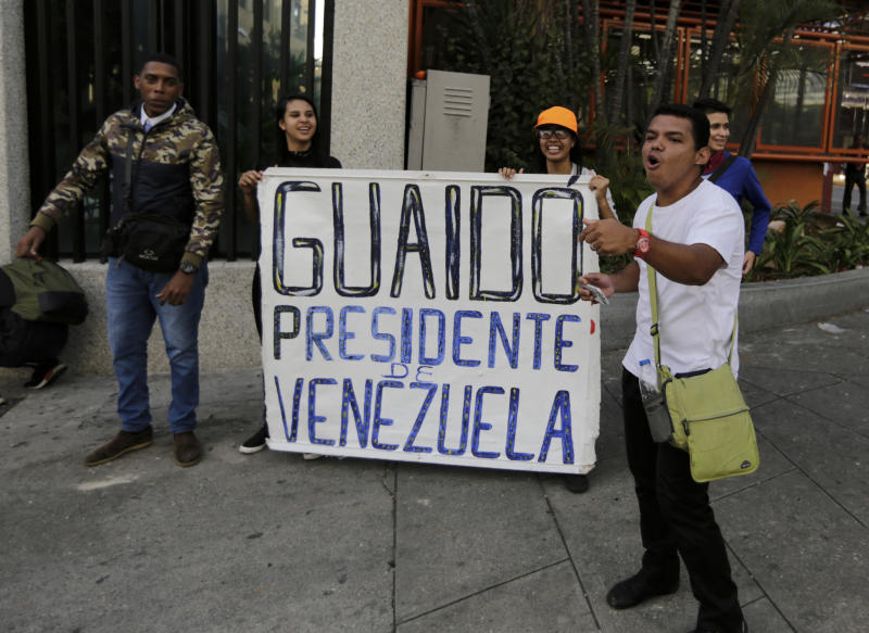 "Anti-government protesters show a sign that reads in Spanish ""Guaido President of Venezuela"" after a rally demanding the resignation of President Nicolas Maduro in Caracas, Venezuela, Wednesday, Jan. 23, 2019. The head of Venezuela's opposition-run congress declared himself interim president at the rally, until new elections can be called.(AP Photo/Fernando Llano)"