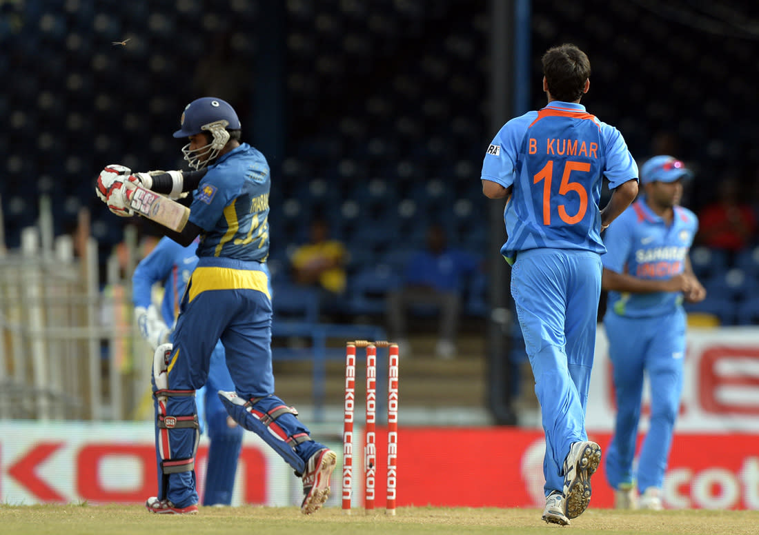 Sri Lankan cricketer Upul Tharanga (L) leaves the field after being dismissed off Indian bowler Bhuvneshwar Kumar (R) during the sixth match of the Tri-Nation series between India and Sri Lanka at the Queen's Park Oval stadium in Port of Spain on July 9, 2013. Sri Lanka is given a target of 178-runs to win after rain interrupted match was tailored down to 26 overs. AFP PHOTO/Jewel Samad