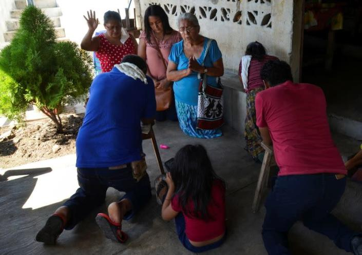 Friends pray in the home of Gerardo Zacarias and his wife Maria Victoria Orozco, who fear their daughter Paola Damaris is among the 19 bodies found shot and burnt in a remote part of northern Mexico, in Catarina