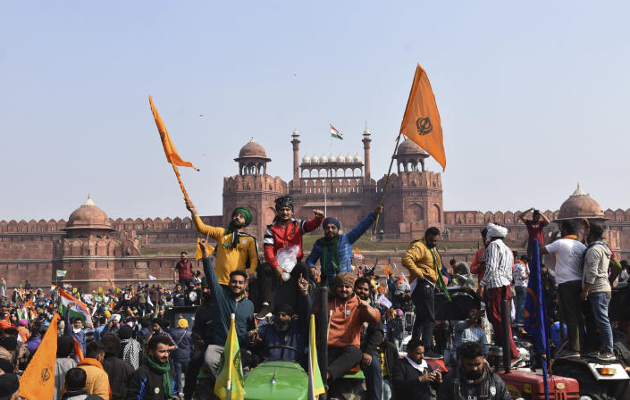 Sikhs wave the Nishan Sahib, a Sikh religious flag, as they arrive at the historic Red Fort monument in New Delhi, India, Tuesday, Jan. 26, 2021. Tens of thousands of protesting farmers drove long lines of tractors into India's capital on Tuesday, breaking through police barricades, defying tear gas and storming the historic Red Fort as the nation celebrated Republic Day. (AP Photo/Dinesh Joshi)