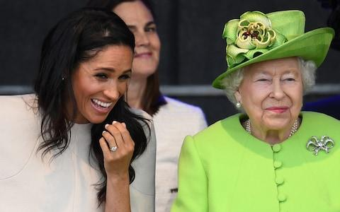 The Duchess of Sussex and Queen Elizabeth II laugh during their first engagement together in June, where they attended a ceremony to open the new Mersey Gateway bridge. - Credit: Jeff J Mitchell/Getty Images