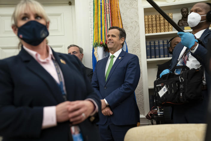 Director of National Intelligence John Ratcliffe looks on as President Donald Trump presents the Presidential Medal of Freedom to former football coach Lou Holtz, in the Oval Office of the White House, Thursday, Dec. 3, 2020, in Washington. (AP Photo/Evan Vucci)