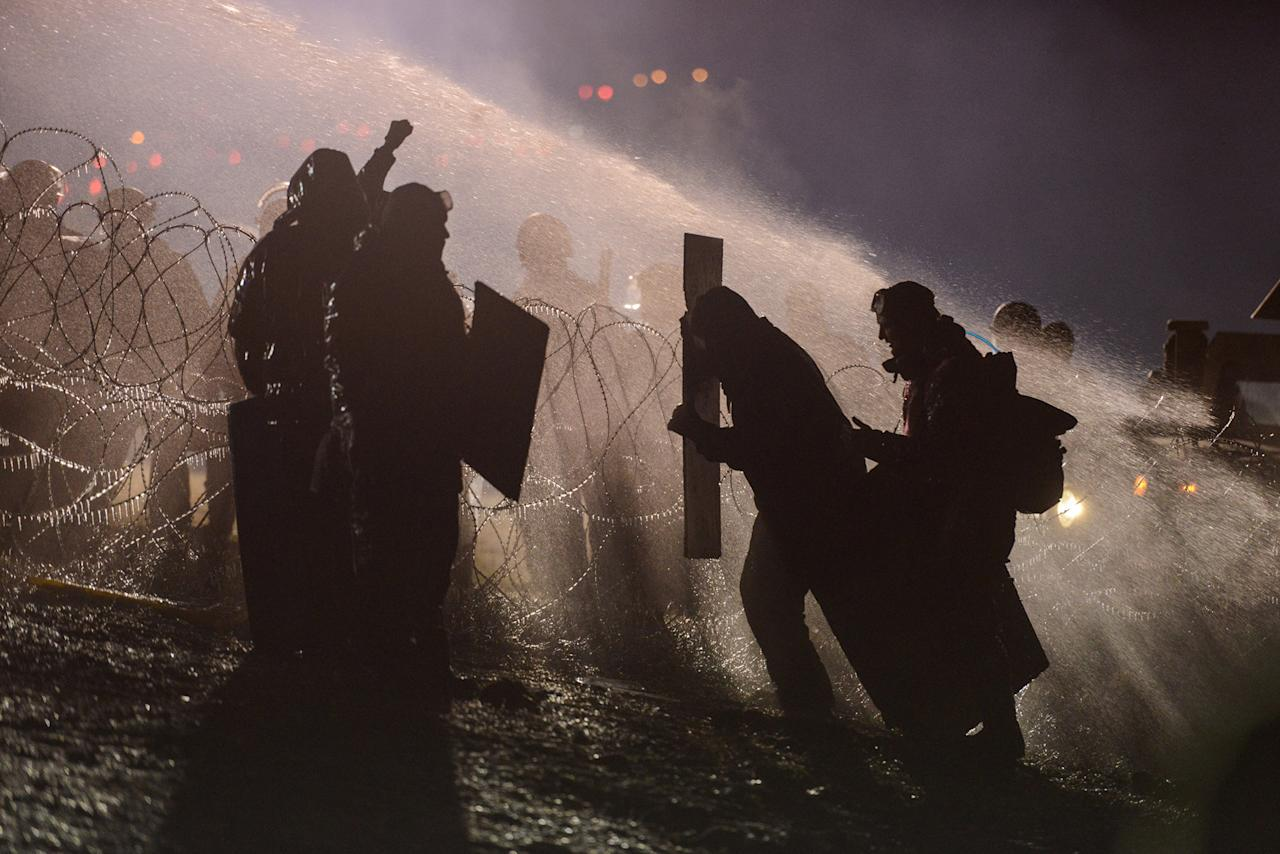 <p>Police use a water cannon on protesters during a protest against plans to pass the Dakota Access pipeline near the Standing Rock Indian Reservation, near Cannon Ball, N.D., on Nov. 20, 2016. (Stephanie Keith/Reuters) </p>