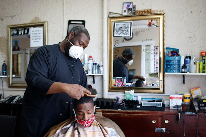Barber Patrick Watkins of Jet Cuts & Styles finishes up a haircut on Darrell Stevens at the reopened barbershop in Athens, Georgia, on April 24.