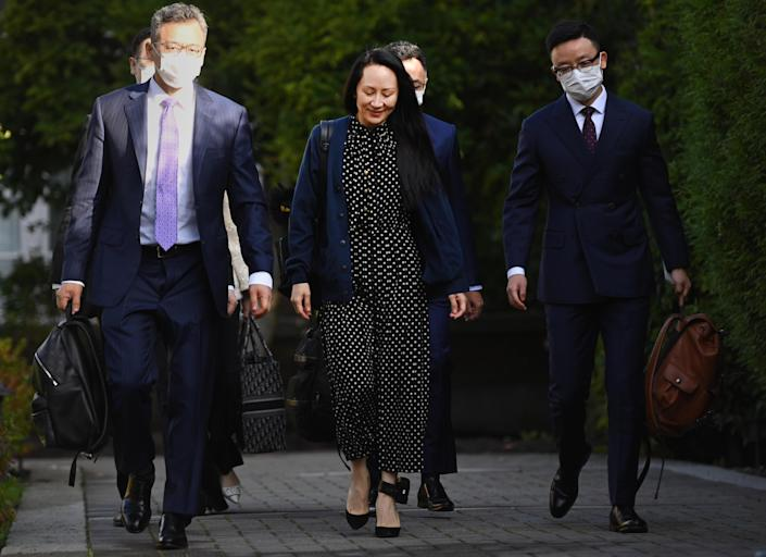 Meng Wanzhou, chief financial officer of Huawei Technologies Co., center, exits her home in Vancouver, British Columbia, Canada, on Friday, Sept. 24, 2021. / Credit: Jimmy Jeong/Bloomberg via Getty Images