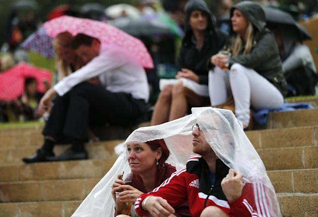 Tennis fans huddle under umbrellas and plastic sheets as they watch Roger Federer of Switzerland play Gilles Muller of Luxembourg on a large TV screen at the All England Lawn Tennis Championships in Wimbledon, London, Thursday, June 26, 2014. (AP Photo/Ben Curtis)
