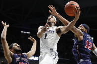 Xavier's Paul Scruggs (1) shoots against St. John's Marvin Clark II (13) and LJ Figueroa, left, in the first half of an NCAA college basketball game, Saturday, March 9, 2019, in Cincinnati. (AP Photo/John Minchillo)