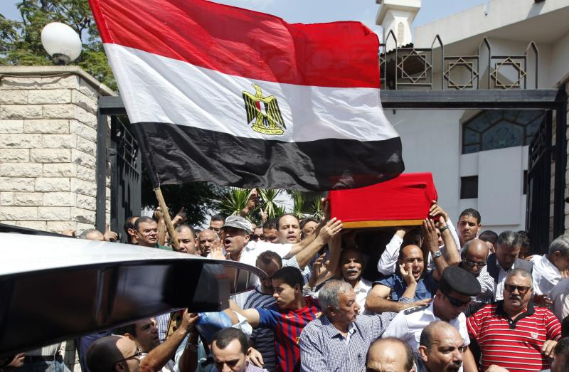 Mourners carry the coffin of Police General Farag, who was killed during a security operation in Kerdasa, at Al-Rashdan Mosque in Nasr City