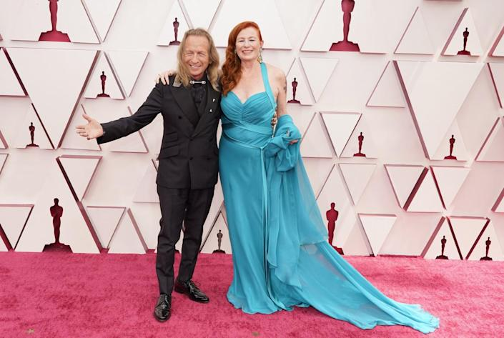 Paul Raci in a black outfit and Liz Hanley Raci in a blue gown with train at the Oscars.