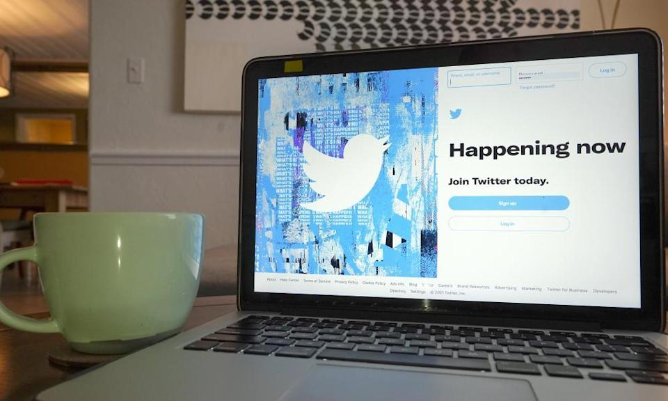 The login/sign up screen for a Twitter account is seen on a laptop computer.