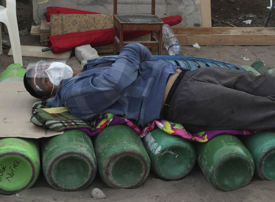 A man sleeps on top of empty oxygen cylinders, waiting for a shop to open to refill his tank, in the Villa El Salvador neighborhood of Lima, Peru, early Thursday morning, Feb. 18, 2021. A crisis over the supply of medical oxygen for coronavirus patients has struck nations in Africa and Latin America, where warnings went unheeded at the start of the pandemic and doctors say the shortage has led to unnecessary deaths. (AP Photo/Martin Mejia)