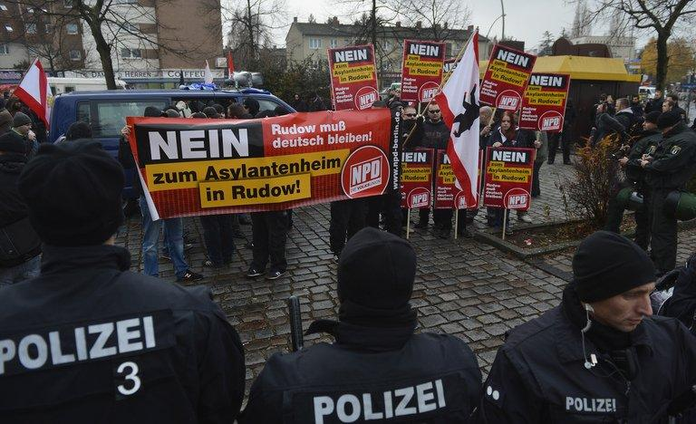 Policemen stand in front of supporters of German far-right party NPD during a demonstration in Berlin on November 24, 2012
