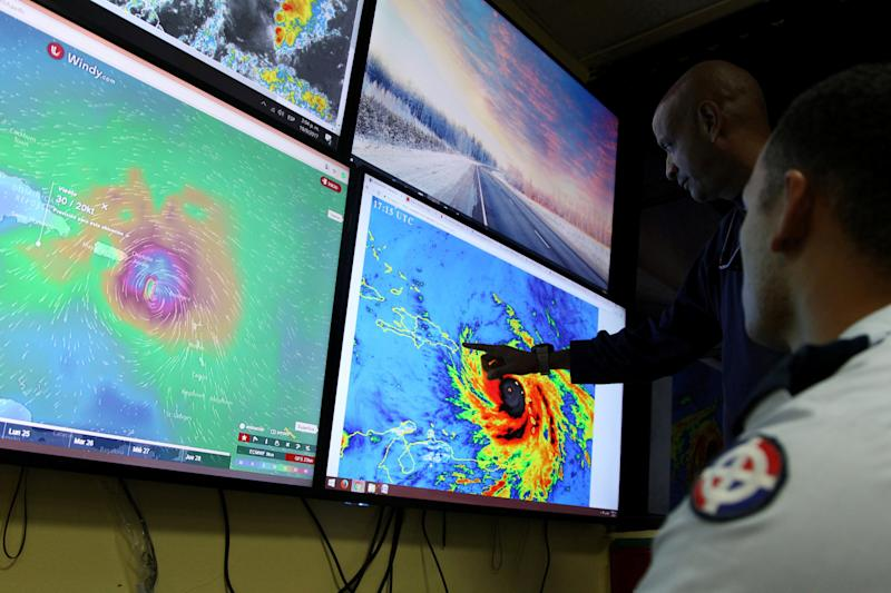 Members of the Emergency Operations Committee (COE) monitor the trajectory of Hurricane Maria in Santo Domingo