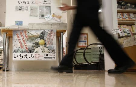 "A staff walks past a poster of a Japanese Manga ""Ichi Efu"", which centres on workers at the Fukushima Daiichi nuclear plant, at a bookstore in Tokyo June 23, 2014. REUTERS/Yuya Shino"