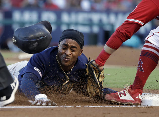 Seattle Mariners' Mallex Smith, left, steals third base before the tag from Los Angeles Angels third baseman David Fletcher during the third inning of a baseball game Saturday, July 13, 2019, in Anaheim, Calif. (AP Photo/Marcio Jose Sanchez)