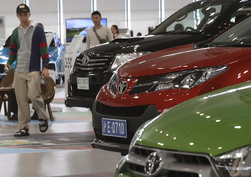 Visitors looks at cars displayed at a Toyota gallery in Tokyo Thursday, May 8, 2014. Toyota's fourth quarter profit dropped slightly despite higher vehicle sales and a weak yen as it spend more on research and development. Toyota Motor Corp. reported Thursday a January-March profit of 297 billion yen ($2.9 billion), down from 313.9 billion yen a year earlier. Quarterly sales rose 12.5 percent to 6.57 trillion yen ($64.5 billion). (AP Photo/Koji Sasahara)