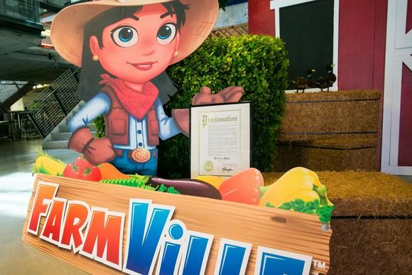 Farmville stand-up sign in front of a red barn, inside a modern building.
