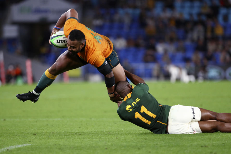 Australia's Samu Kerevi, left, brats the tackle from South Africa's Makazole Mapimpi during their Rugby Championship match on Sunday, Sept. 12, 2021, Gold Coast, Australia. (AP Photo/Tertius Pickard)