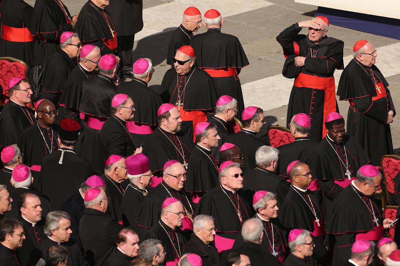 VATICAN CITY, VATICAN - FEBRUARY 27:  Archbishops (purple hats) and cardinals (red hats) wait in St Peter's Square before Pope Benedict XVI's final weekly public audience on February 27, 2013 in Vatican City, Vatican.  The Pontiff has attended his last weekly public audience before stepping down tomorrow. Pope Benedict XVI has been the leader of the Catholic Church for eight years and is the first Pope to retire since 1415. He cites ailing health as his reason for retirement and will spend the rest of his life in solitude away from public engagements.  (Photo by Oli Scarff/Getty Images)