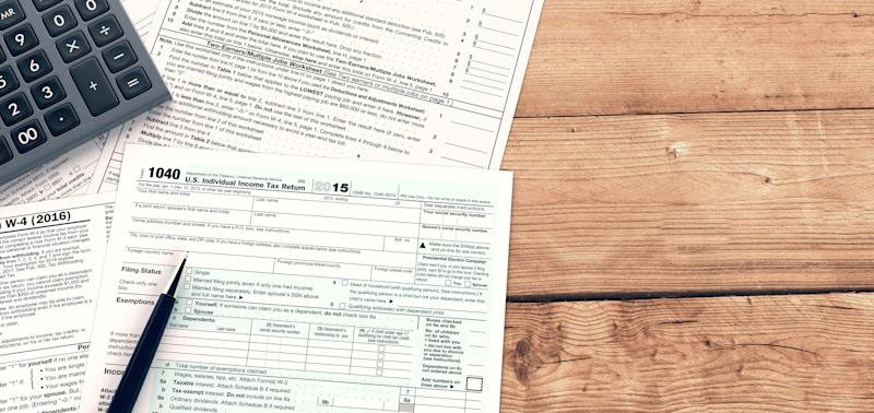Tax forms resting on wooden surface; calculator and pen are on top of tax forms