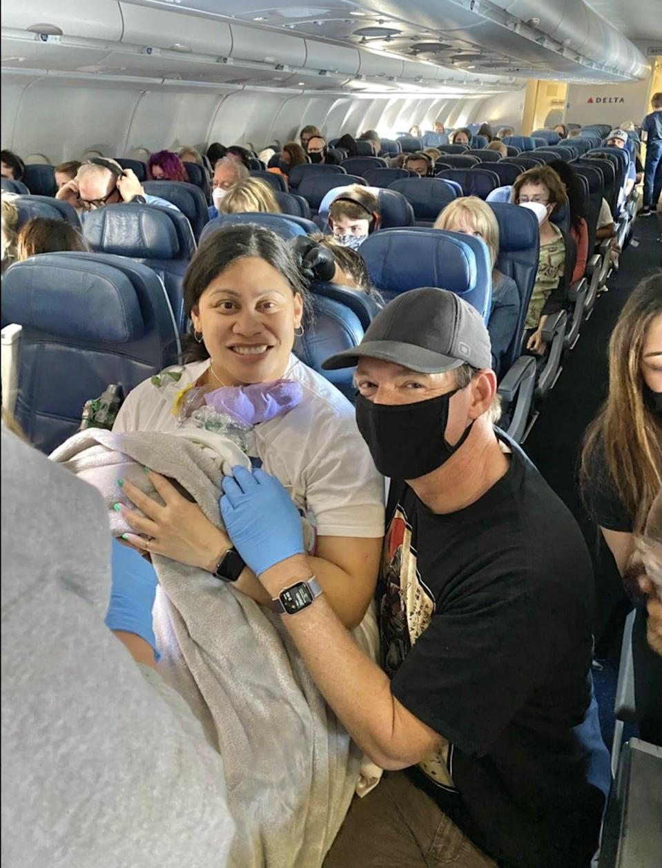 Lavinia Mounga and Dr. Dale Glenn posing after Mounga's gave birth aboard a Delta flight to Hawaii.