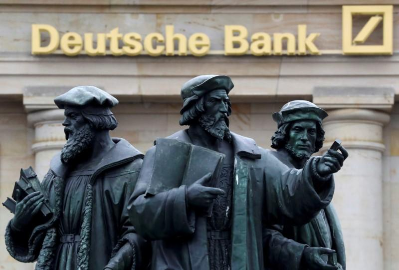 A statue is pictured next to the logo of Germany's Deutsche Bank in Frankfurt