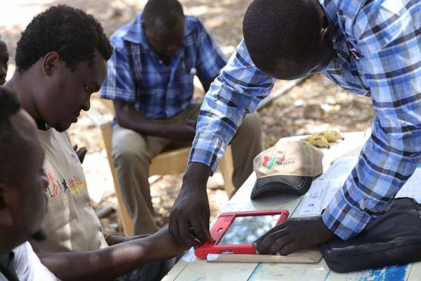 PHOTO: An Officer from the National Integrated Identity Management system (NIIMS) is seen helping a man process his biometric data, May 20, 2019, in Kipcherere, Kenya. (Sopa Images/LightRocket via Getty Images)