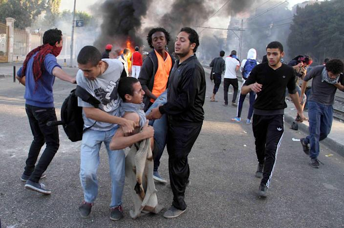 "Supporters of ousted President Mohammed Morsi rescue an injured comrade during clashes with security forces in Cairo, Egypt, Friday, Dec. 6, 2013. Egypt's Interior Ministry says it will no longer allow visits to the country's ousted president, now held in a remote desert prison. Ministry spokesman Col. Gamal Mokhtar said Friday that Mohammed Morsi had delivered four messages ""inciting violence"" against the interim government during a first meeting with his lawyers on Nov. 13. Morsi made a statement through his lawyers saying Egypt will see no stability unless he returns to power. (AP Photo/Khaled Kamel)"