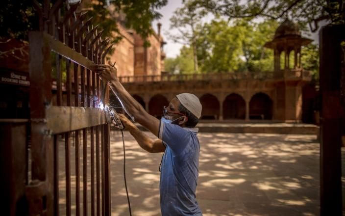 A worker welds a gate near the ticket booking counter at the Taj Mahal - Anindito Mukherjee /Bloomberg