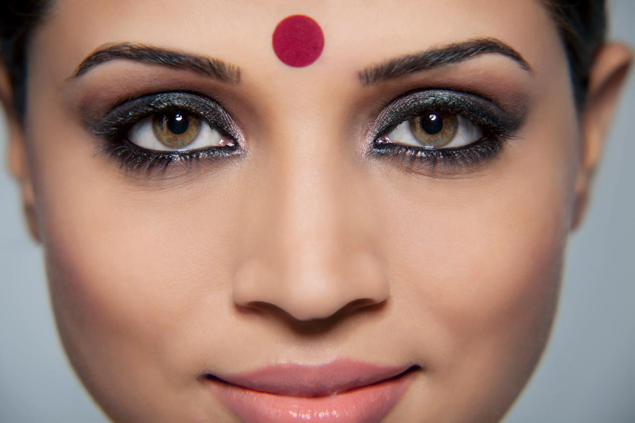<p>The mesmerising coloured dot worn on the center of the forehead, commonly by Hindu and Jain women. The bindi or pottu finds its origins in the Rigveda (Hindu sacred texts). 'Bindu' is considered the point at which creation begins and may become unity. It is also described as the sacred symbol of the cosmos in its unmanifested state.<br />Traditionally, the area between the eyebrows (where the 'bindi' is placed) is said to be the sixth chakra, 'ajna', the seat of 'concealed wisdom'. The bindi is said to retain energy and strengthen concentration. It also represents the third eye. One simple interpretation it is a cosmetic mark used to enhance beauty. In Hinduism, colour red represents honour, love and prosperity, hence it was worn to symbolise these aspects. In meditation, this very spot between the eyebrows is where one focuses his/her sight, so that it helps concentration.<br />The bindi is also normally worn by married women. </p>