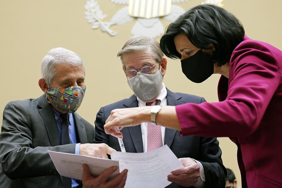 Anthony Fauci, director of the National Institute of Allergy and Infectious Diseases, from left, David Kessler, chief science officer of Covid response at the U.S. Department of Health and Human Services (HHS), and Rochelle Walensky, director of the U.S. Centers for Disease Control and Prevention (CDC), look at a document before the start of a Select Subcommittee On Coronavirus Crisis hearing in Washington, D.C., U.S., on Thursday, April 15, 2021. (Susan Walsh/AP Photo/Bloomberg via Getty Images)