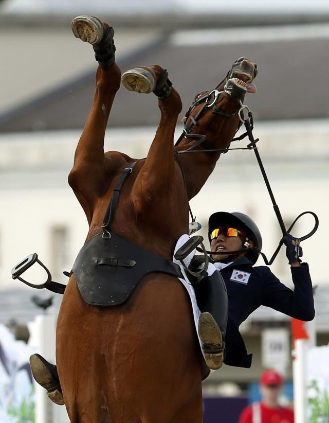 South Korea's Hwang Woojin riding Shearwater Oscar falls during the riding event of the men's modern pentathlon during the London 2012 Olympics at Greenwich Park August 11, 2012. REUTERS/Mike Hutchings (BRITAIN - Tags: SPORT OLYMPICS SPORT EQUESTRIANISM PORT MODERN PENTATHLON TPX IMAGES OF THE DAY)