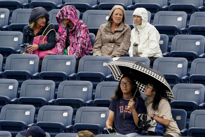 Tennis fans wait out a rain delay during the second round of the US Open tennis championships, Wednesday, Sept. 1, 2021, in New York. (AP Photo/Elise Amendola)